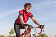 Усмехаясь профессиональный велосипедист дороги во время езды на велосипеде Outdoors стоковые фото