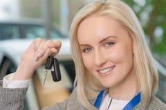Усмехаясь продавец представляя ключ автомобиля Стоковые Изображения RF