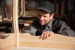 Усмехаясь плотник рассматривает производит мебель стоковое фото
