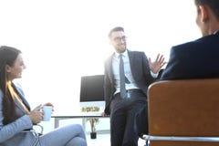 Усмехаясь работа объединяется в команду во время периода отдыха в ярком офисе Стоковое фото RF