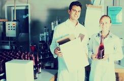 2 усмехаясь работника стоя в упаковывая разделе на manu вина Стоковое Фото