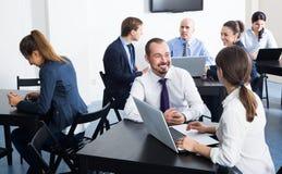 Усмехаясь работники имея производительный день на работе Стоковое Изображение