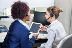 Усмехаясь работники центра телефонного обслуживания обсуждая пока Стоковые Изображения