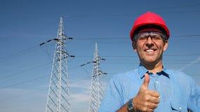 Усмехаясь работник около электрических башен передачи стоковое изображение
