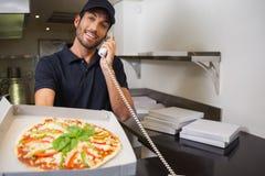 Усмехаясь работник доставляющий покупки на дом пиццы принимая заказ над телефоном показывая пиццу стоковые изображения