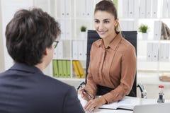 Усмехаясь работник офиса смотря ее коллеги Стоковое Изображение