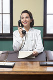 Усмехаясь работник службы рисепшн на работе Стоковая Фотография RF