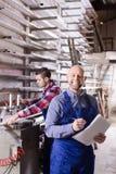2 усмехаясь рабочего класса на фабрике Стоковое Фото