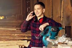 Усмехаясь рабочий класс одел в checkered рубашке говоря телефон около круглой пилы Тимберсы на предпосылке Стоковая Фотография RF