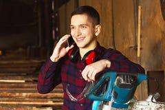 Усмехаясь рабочий класс одел в checkered рубашке говоря телефон около круглой пилы Тимберсы на предпосылке Стоковые Фото