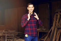 Усмехаясь рабочий класс одел в checkered рубашке нося защитные наушники на лесопилке Тимберсы на предпосылке Стоковое Изображение RF