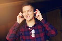 Усмехаясь рабочий класс одел в checkered рубашке нося защитные наушники на лесопилке Тимберсы на предпосылке Стоковые Изображения