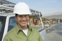 Усмехаясь рабочий-строитель в защитном шлеме тележкой на месте Стоковые Изображения