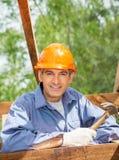 Усмехаясь рабочий-строитель держа молоток на месте Стоковая Фотография RF