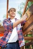 Усмехаясь рабочий-строитель стоя на месте Стоковые Фото