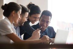 Усмехаясь разнообразные коллеги смеются коллективно обсуждать используя ноутбук стоковое фото