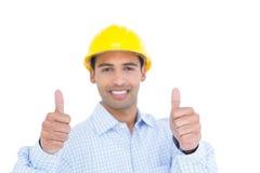 Усмехаясь разнорабочий в желтой трудной шляпе показывать большие пальцы руки Стоковые Изображения