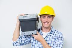Усмехаясь разнорабочий в желтом toolbox нося трудной шляпы Стоковая Фотография RF
