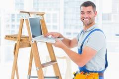 Усмехаясь разнорабочий используя компьтер-книжку лестницей в офисе Стоковые Фотографии RF
