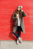 Усмехаясь расслабленное положение молодой женщины и выпивая кофе взятия отсутствующий Стоковые Изображения RF