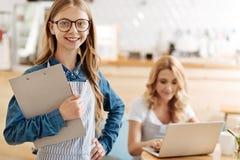 Усмехаясь радостная девушка представляя с держателем листа в кафе Стоковое Изображение