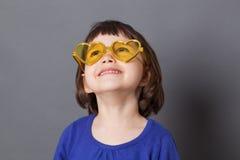 Усмехаясь ребенок дошкольного возраста нося желтые стекла сердц-формы стоковая фотография