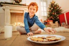 Усмехаясь ребенок принимая печенье пряника дома Стоковое Фото