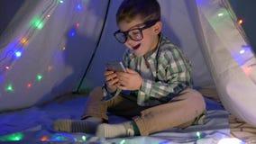 Усмехаясь ребенок смотрит в устройство сидя в вигваме украшенном с гирляндой дома видеоматериал