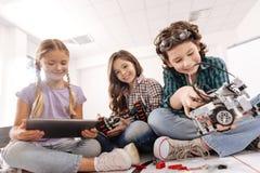 Усмехаясь ребеята школьного возраста используя приборы в студии науки стоковое фото rf