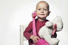 Усмехаясь ребёнок 1-2 годовалое имеющ потеху на белизне Смотреть камеру с игрушками стоковое фото rf