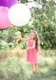 Усмехаясь ребёнок играя с воздушными шарами Стоковое Изображение RF