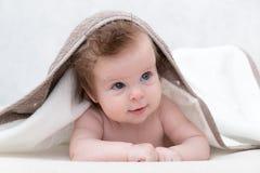 Усмехаясь ребёнок после ливня с полотенцем на голове Счастливый смеясь над младенец нося с капюшоном полотенце лежа на кровати по Стоковое фото RF