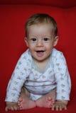 Усмехаясь ребёнок сидя красное одеяло Стоковые Фотографии RF