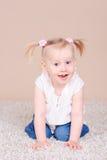 Усмехаясь ребёнок сидя на поле Стоковое фото RF