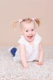 Усмехаясь ребёнок сидя на поле Стоковое Изображение RF