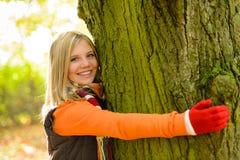 Усмехаясь древесины осени дерева обнимать девушки подростка Стоковая Фотография RF