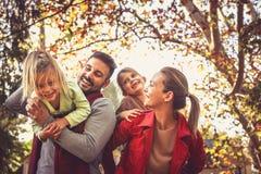 Усмехаясь родители нося дочерей, имеют потеху Стоковое Изображение RF