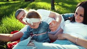 Усмехаясь родители с ребенком ослабляя на одеяле на зеленой траве в парке сток-видео