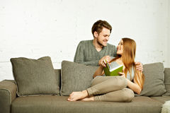 Усмехаясь романтичные пары при книга говоря на кресле Стоковые Изображения RF