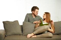 Усмехаясь романтичные пары при книга говоря на софе Стоковая Фотография RF