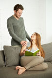 Усмехаясь романтичные пары при книга говоря на софе Стоковые Изображения RF