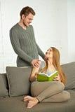 Усмехаясь романтичные пары при книга говоря на софе Стоковое фото RF