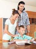 Усмехаясь родители помогая с домашней работой Стоковое Изображение