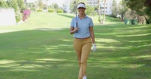 Усмехаясь дружелюбный игрок в гольф женщины идя на курс сток-видео