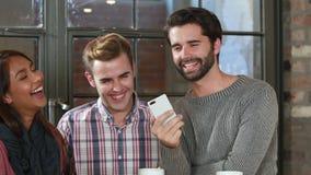Усмехаясь друзья битника обсуждая над smartphone сток-видео
