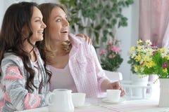 Усмехаясь друзья выпивая чай Стоковая Фотография
