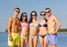 Усмехаясь друзья в солнечных очках на пляже лета Стоковые Изображения RF