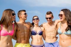 Усмехаясь друзья в солнечных очках на пляже лета Стоковое фото RF