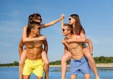 Усмехаясь друзья в солнечных очках на пляже лета Стоковая Фотография RF