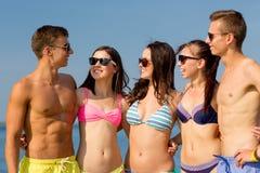 Усмехаясь друзья в солнечных очках на пляже лета Стоковые Фото